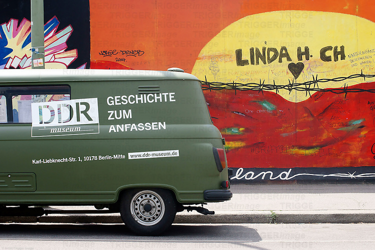 An old Barkas of the DDR Museum stands in front of the East Side Gallery in Berlin.