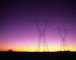 Rows of silhouetted powerlines stretching off into the distance at sunset, Buckeye, Arizona, USA