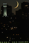 The crescent moon sets In between the buildings in the North Beach district of San Francisco, California.