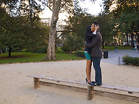 USA. New York City. Union Square Park. A couple of asian lovers hold each other in their arms while stannding up on a wood bench. The woman wears a green tight mini skirt and high-heels shoes, the man casual clothes. 25.10.2011 &copy; 2011 Didier Ruef
