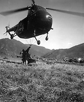 An HRS-1 Sikorsky helicopter hovers close to the ground while Marines hook a cargo net loaded with 1,000 pounds of supplies for transportation to the front 12 miles away.  Ca.  1951. M.Sgt. Ed. Waite.  (Marine Corps)<br /> Exact Date Shot Unknown<br /> NARA FILE #:  127-N-A131970<br /> WAR &amp; CONFLICT BOOK #:  1410