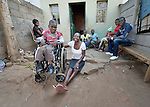 Eric Lovemore, 8, sits with his family outside his house in Bulawayo, Zimbabwe. Lovemore suffered cerebral palsy and uses a wheelchair provided by the Jairos Jiri Association with support from CBM-US.