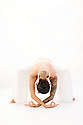 Yogini in devotional forward bend.