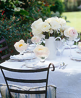 An outdoor table laid with a textured overcloth, white plates and floating peonies