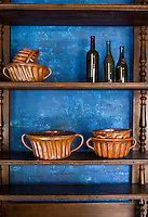 The brick wall behind this set of open shelves in the kitchen has been painted a bright blue