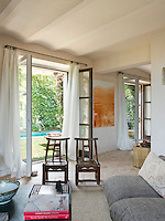 Two pairs of French windows open from the living room onto the small courtyard garden with swimming pool