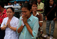 Bystanders pray for freedom as protests led by Buddhist monks calling for the overthrow of the country's military junta pass by. Thousands took to the streets again despite a new threat that the military would shoot on sight any gatherings of over four people.