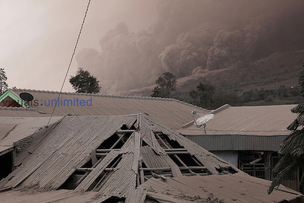 Buildings damaged by and coated in ash with pyroclastic flow descending flank of Sinabung Volcano in background, Sumatra, Indonesia.
