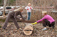 Two Caucasian Women Sawing Log using Old Two-Handed Saw