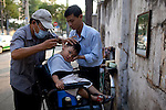 A little boy gets his hair cut on the street in Ho Chi Minh City, Vietnam...Kevin German / LUCEO