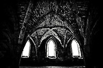 Three Windows deep in the depths of an old Abbey,  bright daylight spilling through, revealing old brickwork and intricate design.
