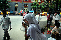 A young Indian lady using a mobile phone at a street in  Kolkata, West Bengal,  India .  Arindam Mukherjee
