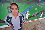 A girl poses in front of a mural in her school in San Luis, a small Mam-speaking Maya village in Comitancillo, Guatemala. With help from the Maya Mam Association for Investigation and Development (AMMID), pupils in the school painted the mural, which highlights cultural values of the Maya community.