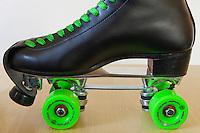 """Michelle's current pair of roller skates.  The boots are Riedell 220's in black, the plate is a Sure Grip Classic plate with toe stop and """"jump bar"""", and the wheels are Rollerbones 98A 57mm in green.  The laces are green waxed hockey laces.   The wheels have Bones China Reds bearings, and there is a Riedell leather toe protector strap installed."""