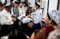 Indian Jewish relatives and friends watch as a circumcision is performed at the Tiphaereth Israel synagogue in Mumbai, India. Photo by Suzanne Lee for Chabad Lubavitch