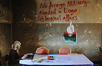 A local journalist works at a special media centre. Graffiti on the wall reads 'No foreign military needed in Libya: it's internal affairs.' On 17 February 2011 Libya saw the beginnings of a revolution against the 41 year regime of Col Muammar Gaddafi.