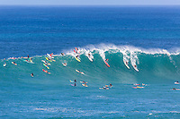 Five surfers drop into a big winter wave at Waimea Bay, North Shore, O'ahu.