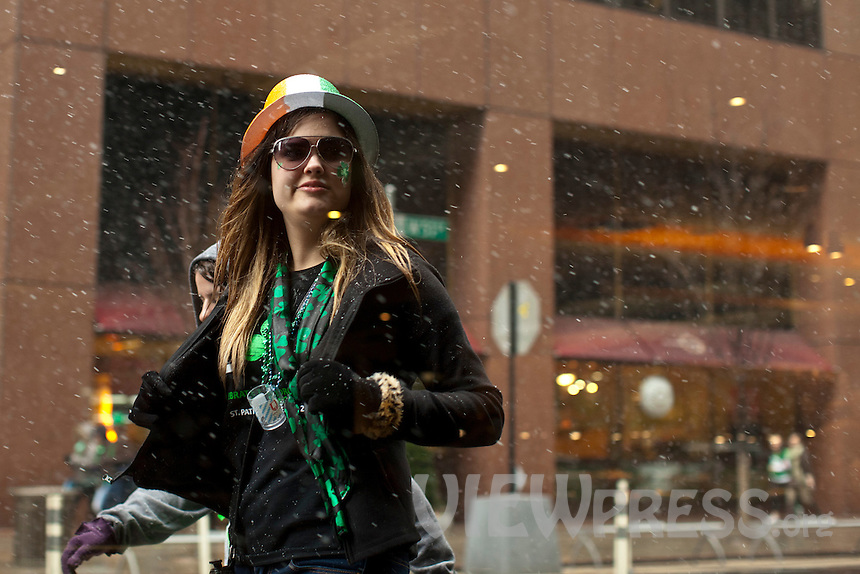 A woman walks during snow as she takes part in the 252nd annual St. Patrick's Day Parade in New York City. Photo by Eduardo Munoz Alvarez / VIEWpress.