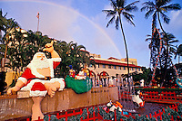 Large Santa Claus flashing the shaka sign sitting on the wall outside Honolulu Hale with a rainbow in the background.