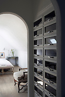 A practical dressing area in the bedroom has been constructed in an arched alcove using reclaimed shelving from old shops