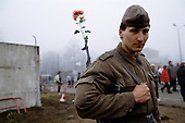 Ostpreu Bendamm, West Germany<br /> November 14, 1989 <br /> <br />  A guard stands with a flower in his gun near the Berlin Wall. Germans gathered as the wall is dismantled and the East German government lifts travel and emigration restrictions to the West on November 9, 1989.