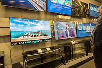 Customers browse Samsung 4K Ultra High Definition televisions in a Best Buy electronics store in New York on Sunday, November 29, 2015. The cost of 4K televisions has come down precipitously this year making them the great hope of retailers as the hot holiday item. (© Richard B. Levine)