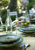 A detail of a table laid for lunch in the garden set with pleasingly rustic green-glazed plates and bowls