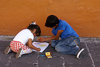 Mexican children playing with a coloring book on the sidewalk, city of Puebla, Mexico