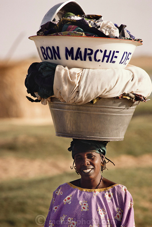 A woman carries her family's laundry down to the Niger River in Kouakourou, Mali. Material World Project.