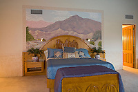 Heavy oak bed shown against mural painted on wall