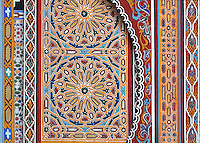 Painted and sculpted wooden panels around a door on the ground floor of the central courtyard area, in a typical Tetouan riad, a traditional muslim house built around a courtyard, built in Moorish style with strong Andalusian influences, next to the Great Mosque or Jamaa el Kebir in the Medina or old town of Tetouan, on the slopes of Jbel Dersa in the Rif mountains of Northern Morocco. Tetouan was of particular importance in the Islamic period from the 8th century, when it served as the main point of contact between Morocco and Andalusia. After the Reconquest, the town was rebuilt by Andalusian refugees who had been expelled by the Spanish. The medina of Tetouan dates to the 16th century and was declared a UNESCO World Heritage Site in 1997. Picture by Manuel Cohen