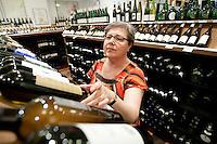 A woman browses through wines on display at Chambers Street Wines in New York, NY, USA, 22 May 2009. The store specializes in naturally made wines from artisanal small producers and has received a Slow Food NYC Snail of Approval.