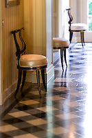 The checked tiled floor of a corridor lined with Empire-style chairs