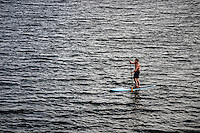 A paddleboarder  navigates his small craft toward the shoreline in the late afternoon sun on Hoover Reservoir in Columbus, Ohio.