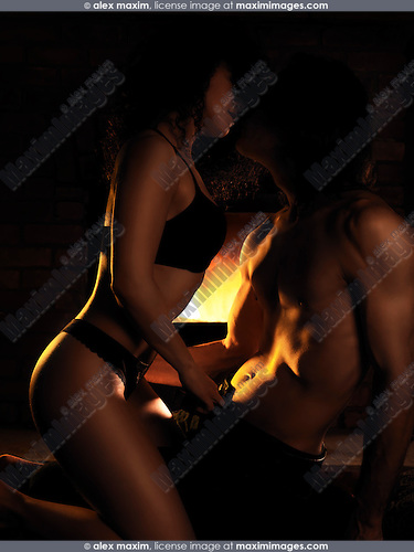 Sensual artistic photo of a sexy young couple making love in front of a fireplace