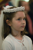 A young girl stands for her first communion sacrament at a Catholic church in Johnstown, OH.<br />