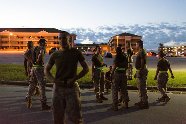 October 22, 2014. Camp LeJeune, North Carolina.<br /> LCpl. Eliyanna Heilig, center, age 19, waits with other Marines of the Ground Combat Element Integrated Task Force after completing the half mile run portion of the Combat Fitness Test (CFT). The CFT includes a half mile run, followed by a series of tests that simulate conditions they could encounter in combat situations.<br />  The Ground Combat Element Integrated Task Force is a battalion level unit created in an effort to assess Marines in a series of physical and medical tests to establish baseline standards as the Corps analyze the best way to possibly integrate female Marines into combat arms occupational specialities, such as infantry personnel, for which they were previously not eligible. The unit will be comprised of approx. 650 Marines in total, with about 400 of those being volunteers, both male and female. <br />  Jeremy M. Lange for the Wall Street Journal<br /> COED