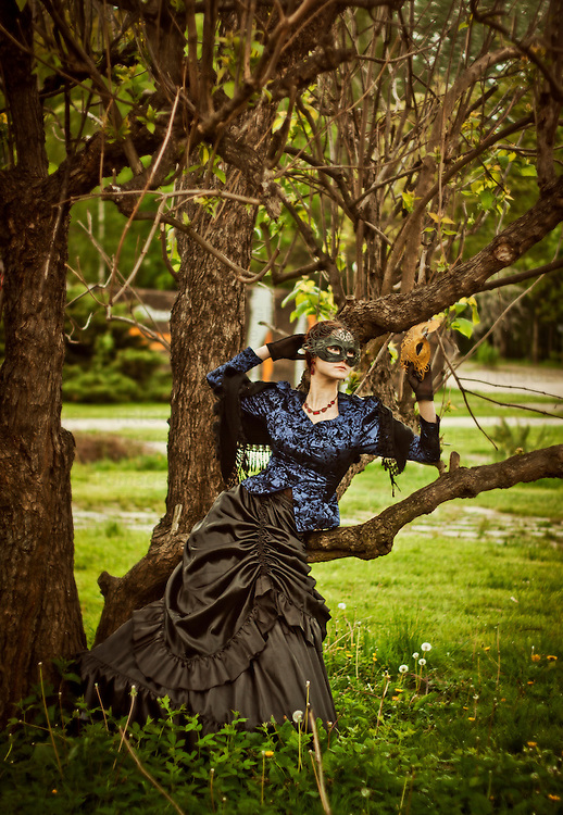atmospheric photo of beautiful young caucasian woman in gothic gown with black mask on her  face, standing among the trees