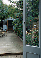 A view through the open door of the kitchen down the length of the teak decking of the garden to a wooden shed