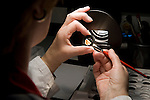 SOLMS, GERMANY - MAY-18-2009 - A technician hand polishes a lens eliminate destined for the Leica Summilux-M 21mm f 1.4 lens, at yet another stage in the lens production process. (Photo © Jock Fistick)