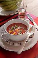 A bowl of Gazpacho reflects the cheerful colour of the place mat on the dining table
