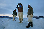 Three Inuit hunters - Gedion Kristiansen, Kristian Eipe, and Ilanguaq Qaernguaq - scan the sea ice near a lead for the seals lying near the breathing holes they have opened in the thinner ice. A changing climate - which shows itself in warming temperatures, earlier summers, later winters, and shrinking and thinning sea ice - threatens the livelihoods and traditions of some of the last subsistence hunters on Earth, the Polar Inuit communities of far Northwest Greenland.