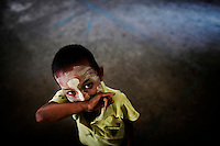 An illegal migrant boy from Myanmar cover his nose as he arrives to a humble school at a rubbish dump site near Mae Sot December 22, 2009. Despite terrible living condition and the fear from being send back to their country, several hundreds illegal migrants from Myanmar live and earn average one US dollar per day collecting plastic at the rubbish dump near the border town of Mae Sot. Myanmar's long standing political crisis has forced millions of people across the border for a better and safer life. The first refugees arrived and set up camps in the Myamar-Thailand border in 1984. Now there are over 140,000 refugees in nine official camps along Thailand's western border. Many more are expected to be in unofficial settlements.  REUTERS/Damir Sagolj (THAILAND)