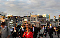 Atmospheric street scene at peak hour with pedestrians and bus passing on the London Bridge, London, UK. St Magnus-the-Martyr's landmark on the northern bank of the river Thames is visible in the background. Picture by Manuel Cohen .