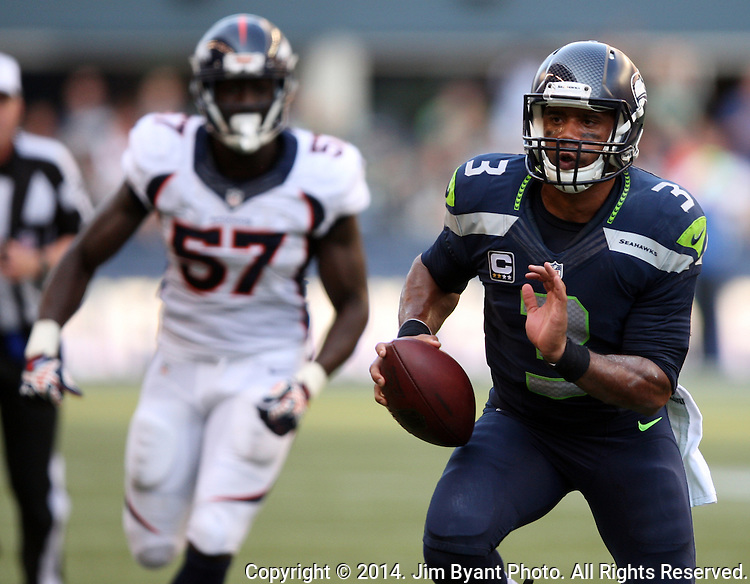 Seattle Seahawks quarterback Russell Wilson (3) looks to pass while scrambling away from against  Denver Broncos linebacker Lamin Barrow (57) during overtime at CenturyLink Field in Seattle, Washington on September 21, 2014.  Wilson completed 24 of 34 passes for 258 yards, two touchdowns and one interception in the 26-20 overtime win against the Broncos.  ©2014. Jim Bryant Photo. All rights Reserved.