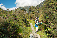 Female hiker arrives in Welcome Flat Hut, Westland National Park, West Coast, World Heritage Area, South Westland, New Zealand