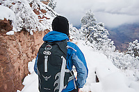 Female hiker hiking on upper section of Bright Angel trail in winter conditions, Grand Canyon national park, Arizona, USA