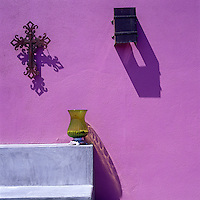 The shapes of an antique crucifix, glass lantern and wall light are outlined against the vivid pink wall of the patio