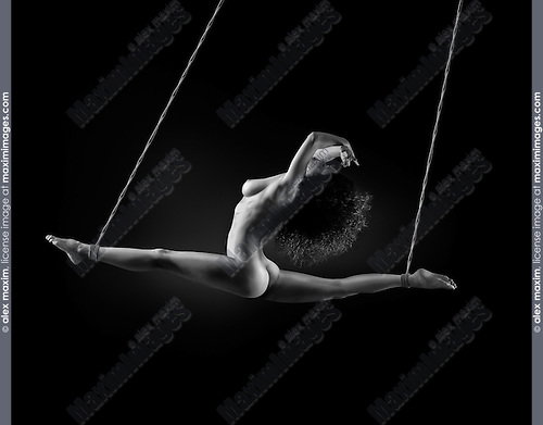 Beautiful nude woman suspended in splits tied with bondage ropes by her ankles on black background. Fine art nude black and white photo.