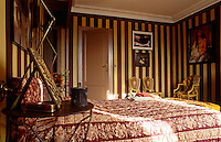 The walls of this bedroom are painted in yellow and aubergine stripes and the bed is covered in a vintage fabric